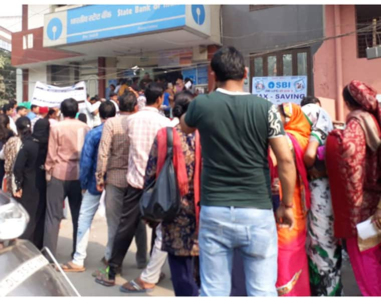 People Throng Banks to Exchange Currency Notes