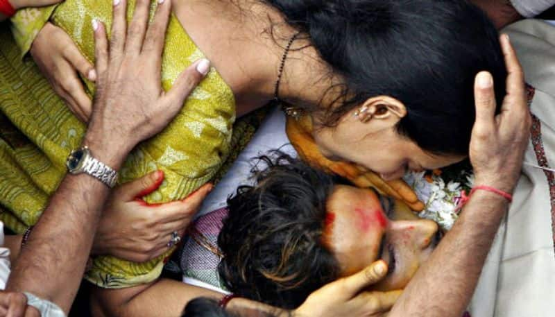 A family member is seen crying over the body of one of the victims of the attack.
