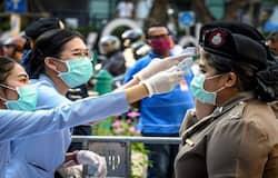थाईलैंड की हेल्थ वर्कर्स महिला पुलिसकर्मियों और अन्य लोगों की जांच करते हुए।