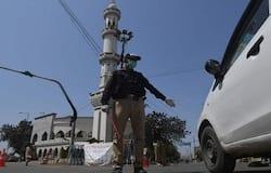 <p>कराची में एक मस्जिद के सामने मास्क पहना पुलिसकर्मी एक कार को आगे बढ़ने से रोक रहा है।&nbsp;</p>