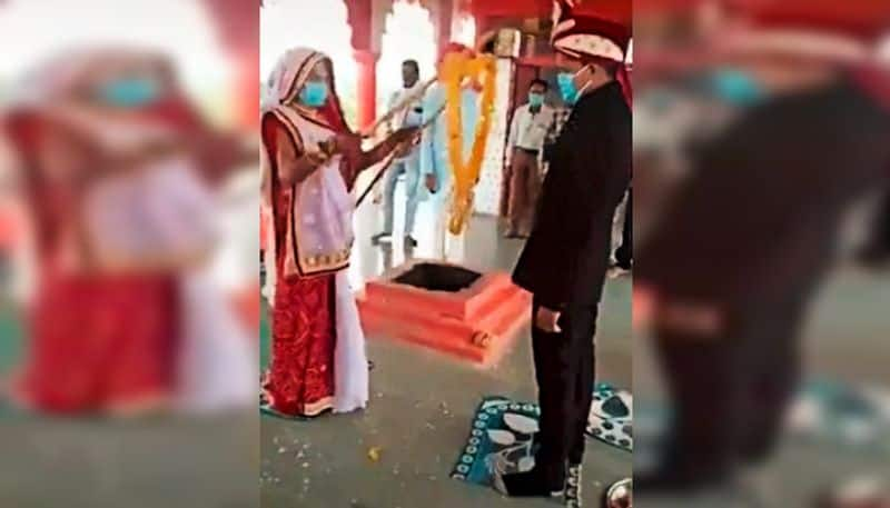 Couple exchanges garlands using sticks to maintain social distancing during wedding, watch the video