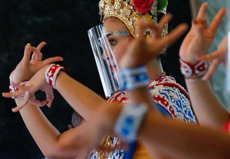 ബാങ്കോക്കില് സുരക്ഷാ മുഖാവരണം ധരിച്ചുകൊണ്ട് വേദിയില് നൃത്തം ചെയ്യുന്ന യുവതി