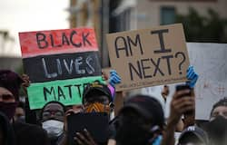 """<p>People hold banners reading """"Black Lives Matter-Am I Next"""", as crowds gather to protest after the death of George Floyd in Washington DC United States on May 29.</p>"""