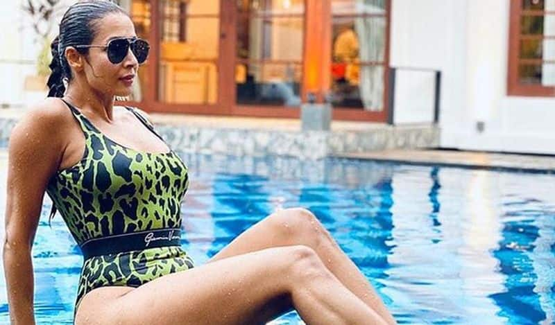 """<p style=""""text-align: justify;"""">Here is another picture of Malaika Arora as she poses with her sunglasses on in a classy printed monokini.</p>"""