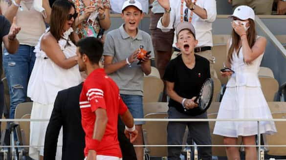 Novak Djokovic presents his title winning racquet and cap to small fan's after win the French Open 2021 spb