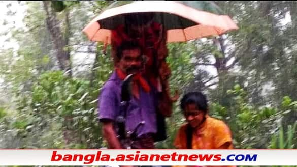 Karnataka father holds umbrella to protect daughter from rain as she attends online class by the road ALB