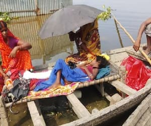 emotional picture of bihar floods parents travelling 10 km by boat for treatment of son kpr