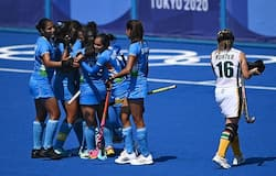 Vandana Katariya (covered) celebrates with teammates after scoring against South Africa during their women's pool A match of the Tokyo 2020 Olympic Games field hockey competition, at the Oi Hockey Stadium in Tokyo on July 31, 2021