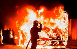 A fireman stands at a burning bus in Braamfontein, Johannesburg, South Africa, Tuesday, Oct. 25, 2016. Rioters in South Africa set a police vehicle on fire Tuesday and stoned vehicles near a Johannesburg university that has been the scene of sometimes violent protests by students demanding free education. The violence broke out in streets near the University of the Witwatersrand at around the same time that student protesters met and marched off the campus, South African media reported.
