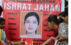 Supporters hold candles in front of a banner bearing the portrait of Ishrat Jahan during a protest in Ahmedabad on July 6, 2013